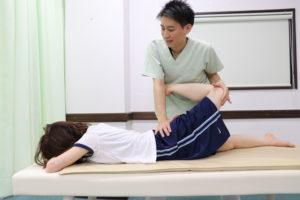 大腿直筋のストレッチを受けている女性と施術者の写真