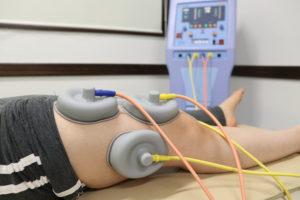 大腿四頭筋へ電気療法を行なっている写真