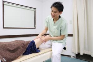 大腿四頭筋へ手技療法を行なっている写真