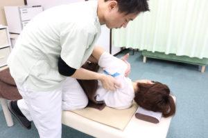 肩甲骨モビリゼーション手技を行う施術者と、それを受けている肩こりの患者様の写真