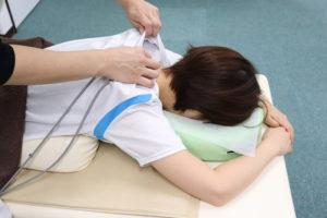 肩こりで電気治療を受けている患者様の写真
