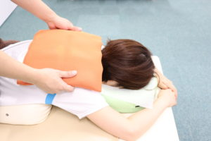 肩こりでホットパックによる温熱療法を受けている患者様の写真