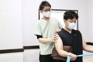 大分ごとう整骨院で肩のチューブトレーニングを行なっている写真