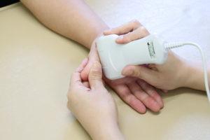 ばね指(母指)のエコー検査を行なっている写真